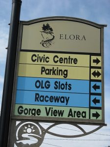 A sign downtown Elora with arrows pointing towards Civic centre, Parking, OLG slots, Raceway and Gorge View Area